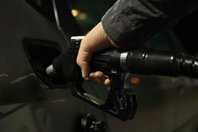 A Man Filling Up a Vehicle with Gas