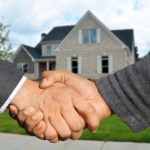Real Estate Parties Shake Hands in Front of a Newly Sold Home in Maryland